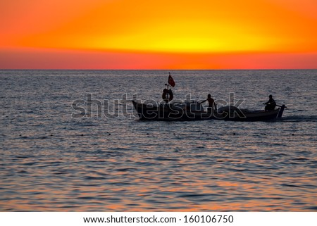 Fishing boat on the water and dramatic clouds at sunrise