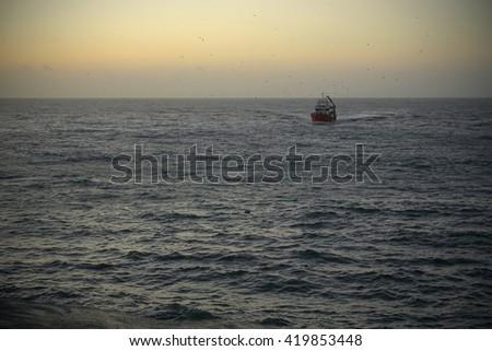 fishing boat returning to harbor - stock photo
