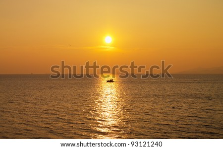 fishing boat sails under the sunset