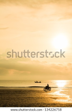Fishing boat sunrise with motorcycle near the beach