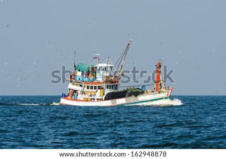Fishing boat trawler in the Gulf of Thailand and birds following. - stock photo