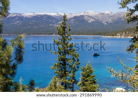 fishing boat trolling in Lake Tahoe, clear blue water reflecting the blue sky - stock photo