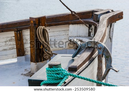 Fishing boat with anchor and ropes moored at the quay in harbor.