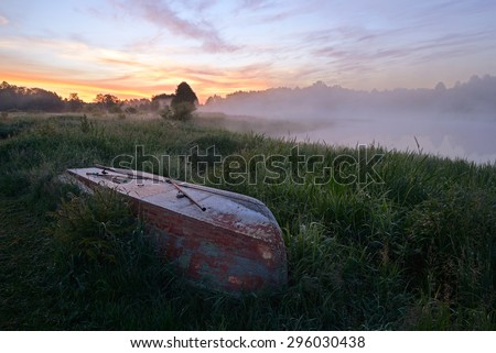 Fishing boat with fishermen gear lies on the banks of the river in the early morning fog - stock photo