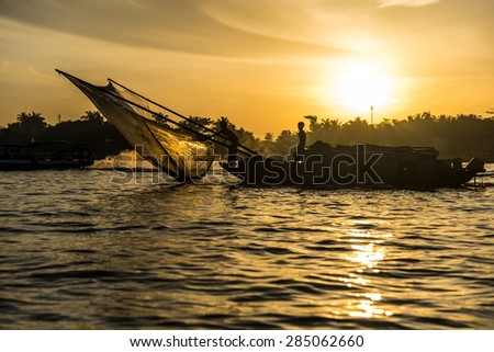 Fishing boat with fishnet on the Mekong River at sunrise. Can Tho, Vietnam.