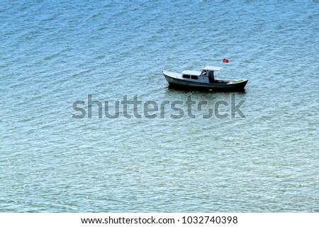 Fishing boat with Turkish flag on blue sea in Turkey.