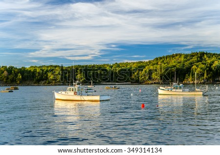 Fishing Boats Anchored in Harbor at Sunset - stock photo