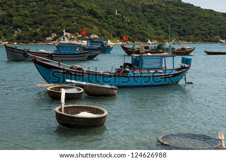 Fishing boats and coracles in the bay - stock photo