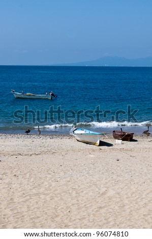Fishing boats and nets drying in the sun with pelicans - stock photo