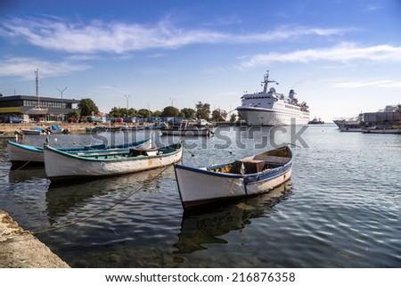 Fishing boats and passenger ship - stock photo