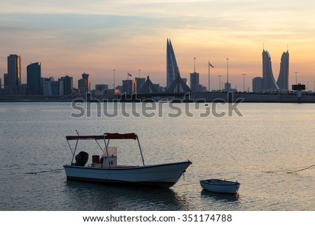 Fishing boats and the skyline of Manama at sunset.  Kingdom of Bahrain, Middle East