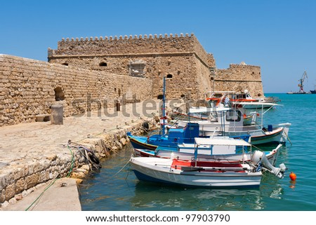 Fishing boats and Venetian Fortress in Heraklion harbor. Crete, Greece - stock photo