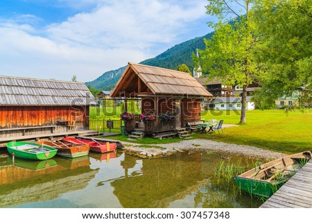 Fishing boats and wooden cabins on shore of Weissensee lake in summer landscape of Carinthia land, Austria