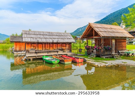 Fishing boats and wooden houses on shore of Weissensee lake in summer landscape of Carinthia land, Austria
