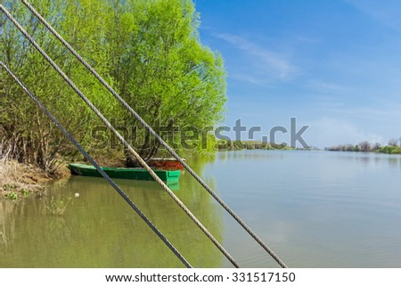 Fishing boats are tied to a tree, marooned to the river shore. - stock photo