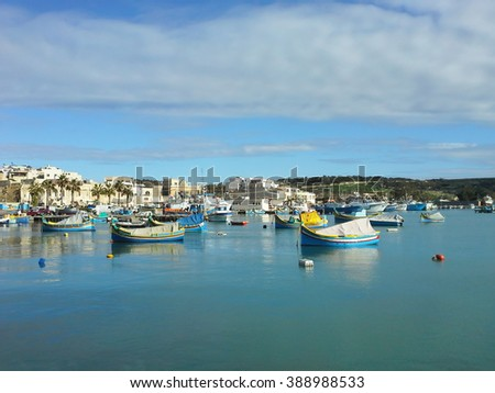 fishing boats at the pier on the Mediterranean sea in the reflection of the blue water against clear sky with clouds at Sunny day