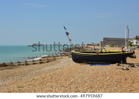 Fishing boats drawn up on the beach a Worthing, West Sussex, England. With unrecognizable people in background