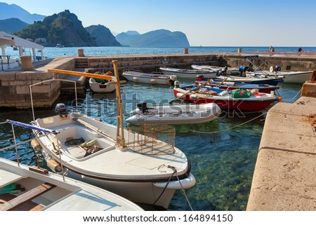 Fishing boats float moored in Adriatic sea water. Petrovac town, Montenegro