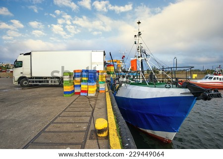 Fishing Boats in a Harbour,loading fish on refrigerated vehicles - stock photo