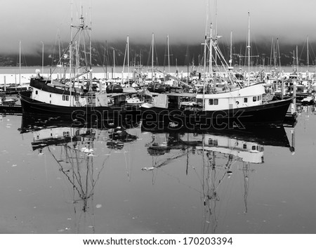 Fishing boats in an Alaskan harbor in winter with reflections and floating ice in black and white - stock photo
