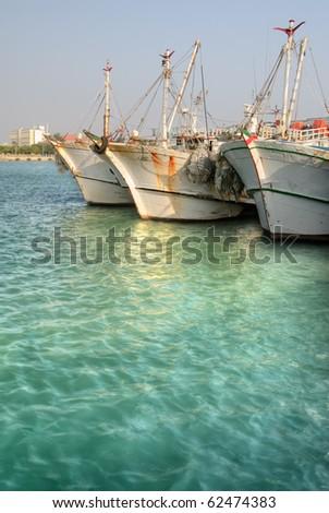 Fishing boats in harbor over beautiful water of sea in Taiwan. - stock photo