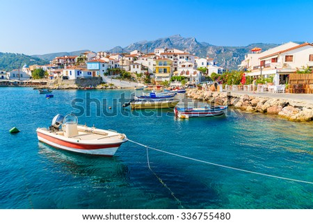 Fishing boats in Kokkari bay with colourful houses in background, Samos island, Greece - stock photo