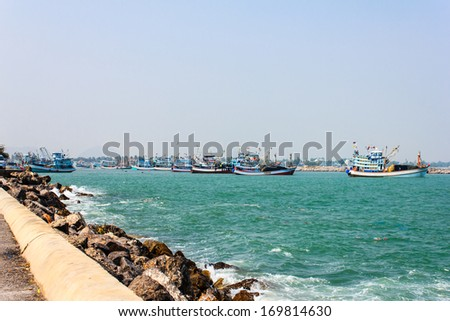Fishing boats moored alongside the pier are a number - stock photo