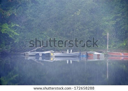 Fishing boats moored to a dock, surrounded by mist.