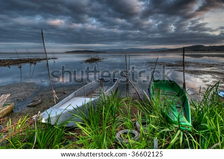 Fishing boats on lake shore in early morning - stock photo