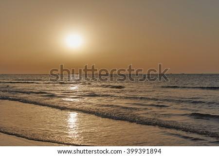 Fishing boats on the horizon returning at sunset - stock photo