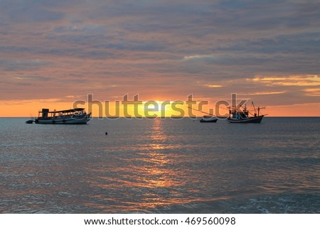 Fishing boats on the sea with sunset background.
