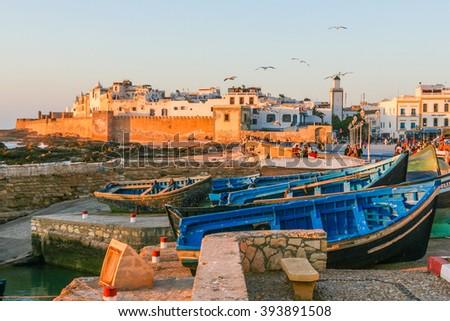 Fishing boats on the shore near the walls of the medina - stock photo