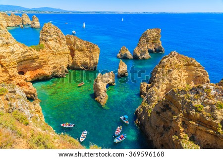 Fishing boats on turquoise sea water at Ponta da Piedade, Algarve region, Portugal - stock photo