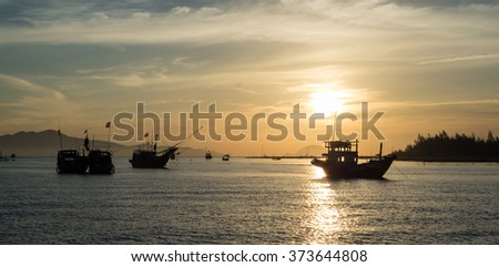 Fishing boats returning to port at sunrise on the Cua Dai river near Hoi An in Vietnam. - stock photo