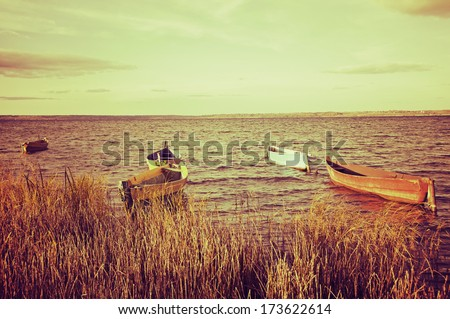 Fishing boats shoreline of a large lake with a retro effect - stock photo
