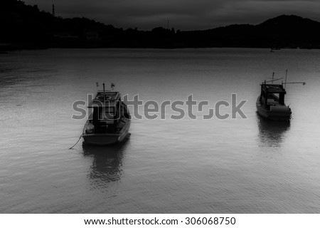 Fishing boats, two boats parked outside location with air like a dark wave during a rain storm force winds made the ship shiver. - stock photo