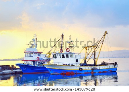 fishing boats under a sunset in a fishing harbor - stock photo