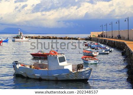 Fishing boats under cloudy sky in Koroni harbor, Greece