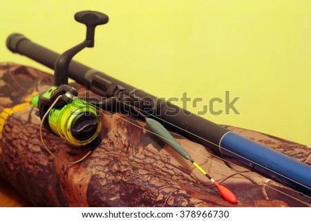 fishing bobber with a fishing rod on a camouflage background - stock photo