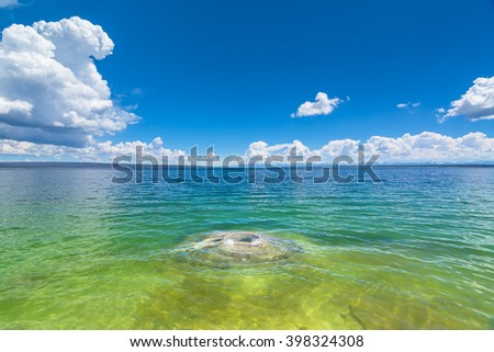 Fishing Cone Geyser, Yellowstone National Park with blue and a little cloudy sky.  This picture intentionally indicates how colorful and what the environment it is in the area. - stock photo