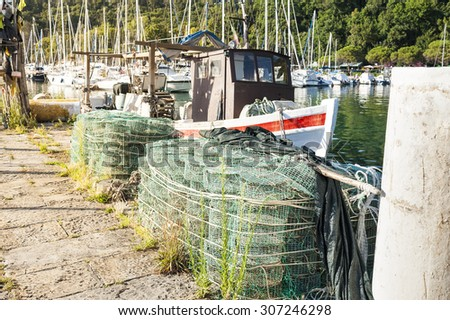 Fishing creels on the pier in the background fishing boat - stock photo