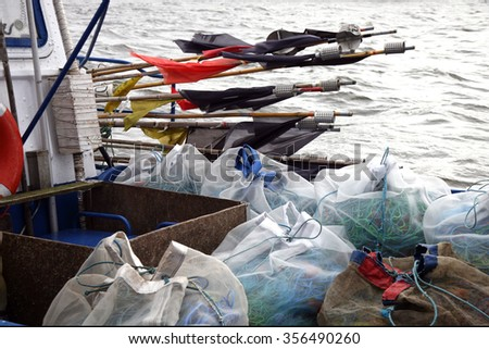 Fishing equipment net and makers. Cutter after fishing by dark, stormy day. - stock photo