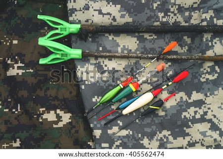 Fishing floats and two rusty, old fishing rod holder. Placed on camouflage clothes of two colors. - stock photo