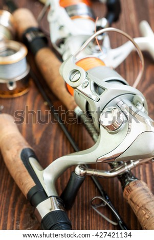 Fishing gear - fishing spinning, fishing line, hooks and lures on wooden background