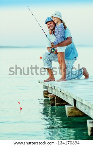 Fishing - girl with father fishing on the pier - stock photo