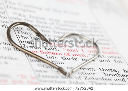 Fishing hooks on the Bible with focus on a very popular text in Matthew 4:19 where Jesus calls disciples to be fishers of men. All copyright items have been deleted. - stock photo