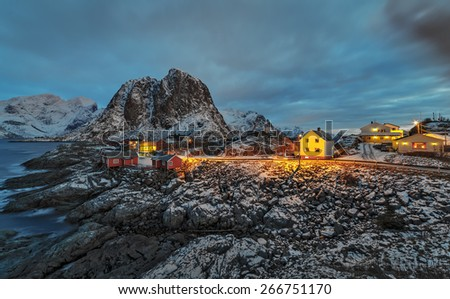 Fishing hut (rorbu) in the Hamnoy and Lilandstinden mountain peak at sunset - Reinefjorden, Reine, Lofoten islands, Norway - stock photo