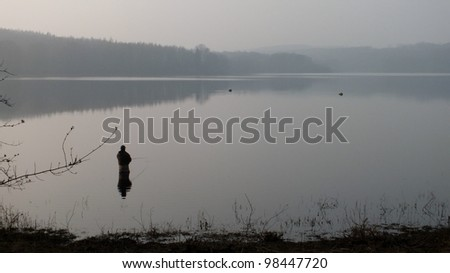 fishing in a tranquil lake at dusk - stock photo