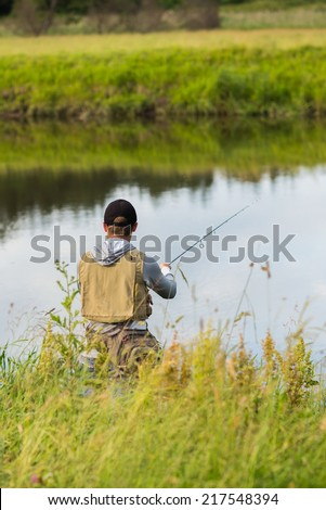 Fishing in river.A fisherman with a fishing rod on the river bank. Man fisherman catches a fish.Fishing, spinning reel, fish, Breg rivers. - The concept of a rural getaway. Article about fishing.