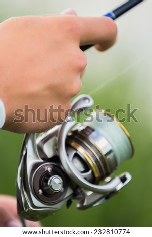 Fishing in river.A fisherman with a fishing rod on the river bank. Man fisherman catches a fish.Fishing, spinning reel, fish, Breg rivers. - The concept of a rural getaway. Article about fishing. - stock photo